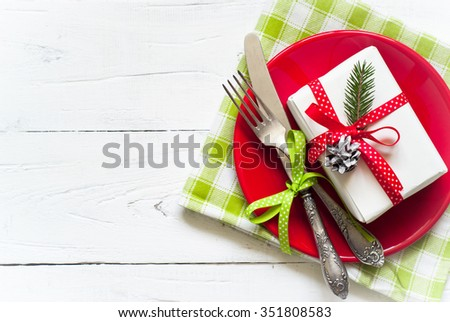 Christmas table setting with gift at white table. Top view, copy space. - stock photo