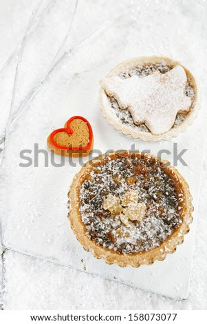 christmas  tart with mincemeat and tart with marzipan tree  on white snow festive background - stock photo