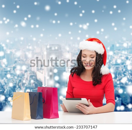 christmas, technology and people concept - smiling woman in santa helper hat with shopping bags and tablet pc computer over snowy city background - stock photo