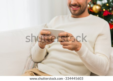 christmas, technology, people and holidays concept - close up of smiling man with smartphone at home - stock photo