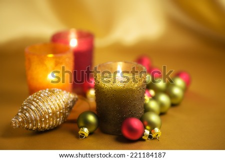 Christmas theme - candles and baubles on gold background.  - stock photo