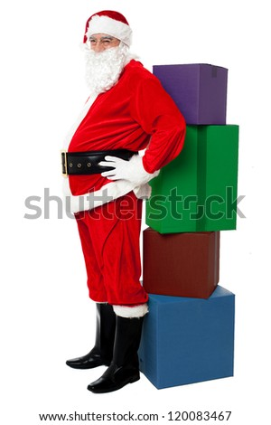 Christmas Theme. Happy Santa Claus leaning over colorful pile of Xmas presents - stock photo