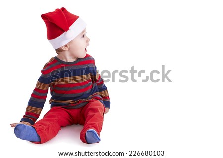Christmas time: Baby boy isolated on white, with a Santa cap,  looking amazed on a side - stock photo