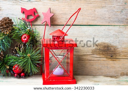 Christmas time interior decorations on the rustic background with candle lamp and fir tree - stock photo
