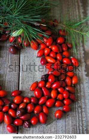 Christmas time table decoration with rose hips and tea with christmas tree branches - stock photo