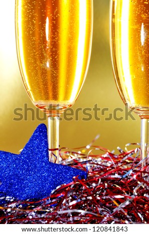 christmas toast: a pair of glasses of champagne and some christmas ornaments on a golden background - stock photo