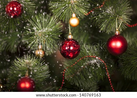Christmas toys on a Christmas tree under snow - stock photo
