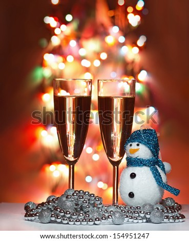 christmas toys, wine glasses and snowman against Christmas lights  - stock photo