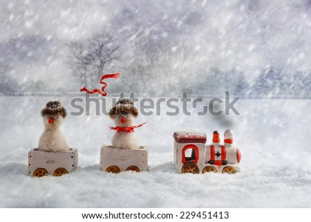 Christmas train set carrying snowmen, one with flying knitted scarf - stock photo