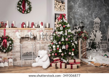Christmas tree and fire-place, toy bear, candles and gifts - stock photo