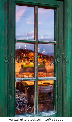 Christmas tree and fireplace seen through a wooden window - stock photo