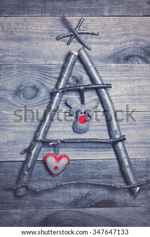 Christmas tree arranged from sticks, twigs, driftwood on wooden background. Handmade red and green heart and Rudolph reindeer made from felt hanging on tree. Craft. - stock photo