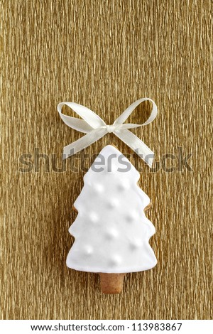 Christmas tree background. Ginger and Honey cookie in the shape of a fir tree with white sugar decoration and bow on the gold wrapping paper background - stock photo