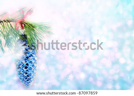 Christmas tree branch holding a pine cone ornament against a beautiful blue background with copyspace. - stock photo