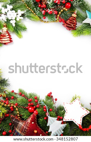 Christmas tree branch with red berries and decorations on white background - stock photo