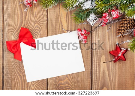 Christmas tree branch with snow and blank greeting card on wooden table. Top view - stock photo