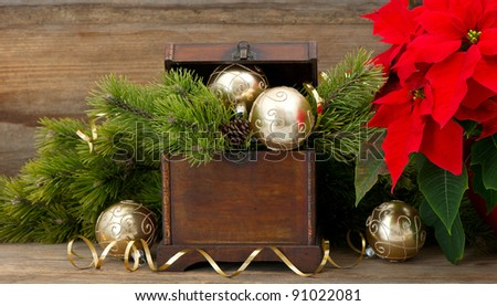 christmas tree brunch with golden decoration, vintage wooden box and red christmas flower poinsettia - stock photo