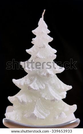 Christmas tree candle on black background - stock photo