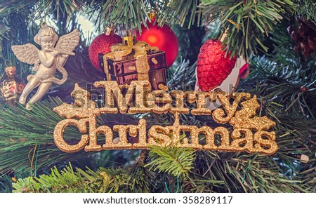 Christmas tree colored ornaments, golden write Merry Christmas, globe hanging, snow flake, green tree, firs, close up. - stock photo