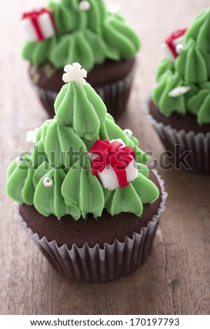 christmas tree cupcake decorating with gift box on the table. - stock photo