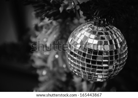 Christmas tree decorated with mirror disco ball. Black and white. Aged photo. - stock photo