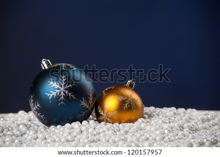 Christmas tree decoration toys lying on artificial snow on blue background with copyspace - stock photo