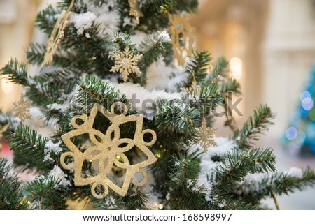 Christmas tree decoration with snow and a gold star - stock photo