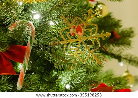 Christmas tree decorations closeup in evening light. Selective focus on golden snowflake. - stock photo