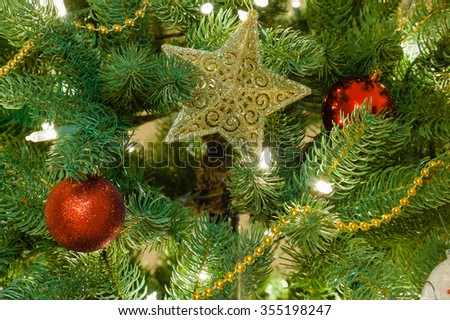 Christmas tree decorations closeup in evening light. Selective focus on star - stock photo