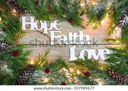 Christmas tree garland border with snow, lights, and the words Hope, Faith, Love on antique rustic wooden background - stock photo