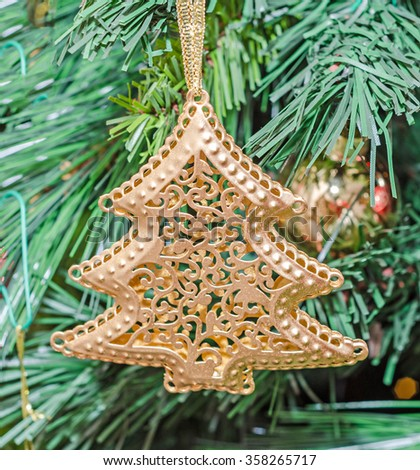 Christmas tree golden ornament, globe hanging, snow flake, green tree, firs, close up. - stock photo