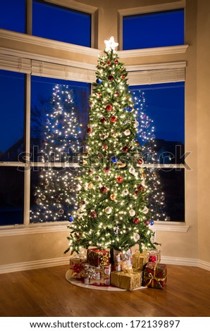 Christmas tree lit up and gifts under the tree - stock photo