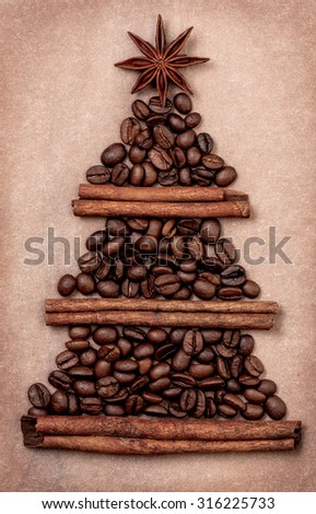 Christmas tree made of cinnamon sticks and coffee beans, star anise on a paper background - stock photo