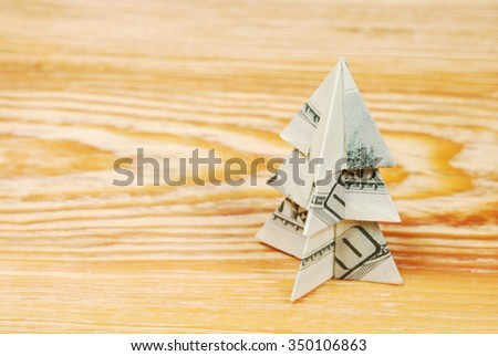 Christmas tree made of hundred dollar bills on a wooden board  - stock photo