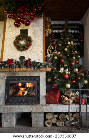Christmas tree near burning fireplace decorated with christmas wreath - stock photo