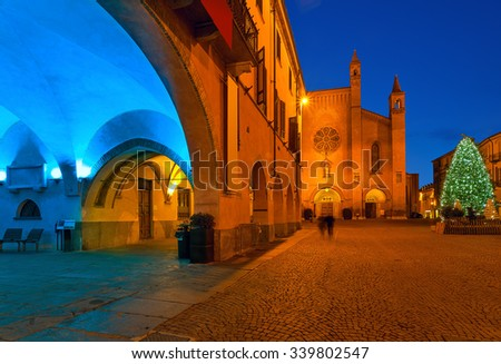 Christmas Tree on town square and cathedral on background at evening in Alba, Piedmont, Northern Italy. - stock photo