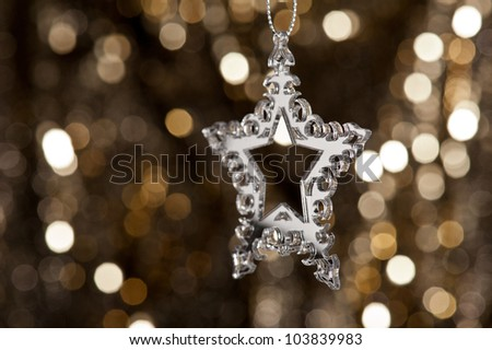 Christmas tree ornament with mirror effect over golden background - stock photo
