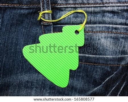 Christmas tree shape label tag on blue jeans - stock photo
