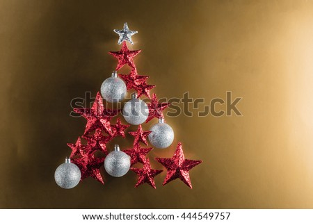 Christmas tree shape with red stars and silver baubles over color background - stock photo
