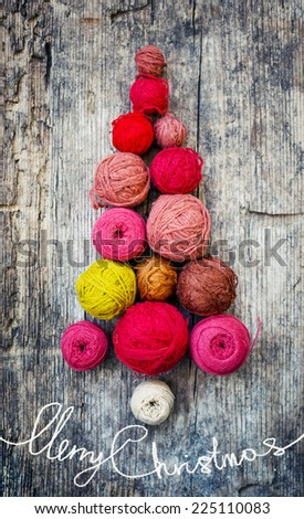 Christmas tree shaped by balls of yarn on wooden background/christmas concept background - stock photo