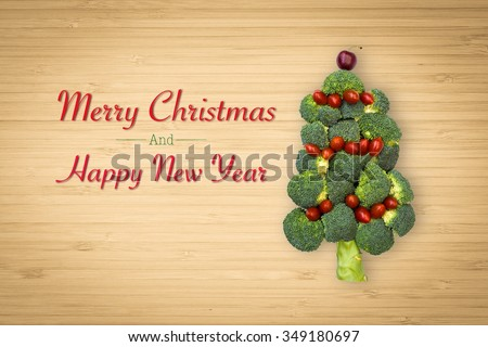 Christmas tree shaped vegetable decoration celebration concept idea: Happy new year and Merry Christmas veggie decorative symbolic design with red and green food on wood cutting board background  - stock photo