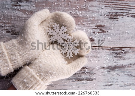 Christmas tree toys like silver snowflakes   in hands  dressing in white  mittens on wooden table top view with copy place - stock photo