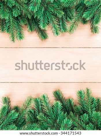 Christmas tree twigs of spruce on a wood background arranged in border pattern - stock photo