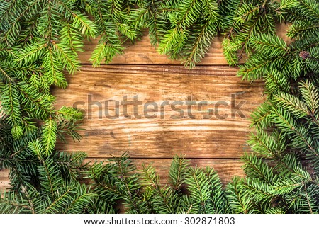 Christmas tree twigs of spruce on a wood background arranged in frame pattern useful as holiday background in vintage style. - stock photo