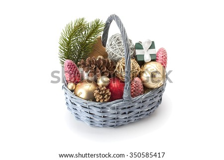 Christmas tree twigs , shiny balls and cones in the basket isolated on a white background - stock photo