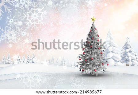 Christmas tree with baubles and star against snowy landscape with fir trees - stock photo