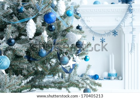 Christmas tree with blue and white toys in the interior / Christmas card with white and blue decor - stock photo
