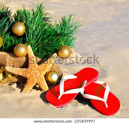 Christmas tree with christmas balls, slippers and starfish on the sand on beach - stock photo