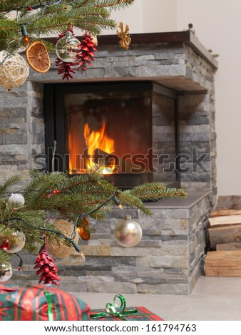 Christmas tree with christmas presents by the lit fireplace - stock photo