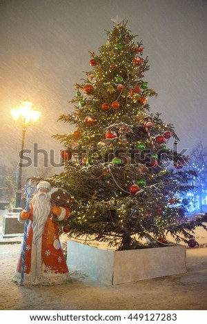 christmas tree with figure of santa claus on winter snowy city street at night - stock photo